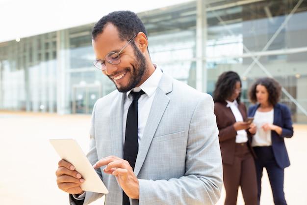 Hombre de negocios alegre que usa la tableta afuera