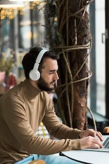 Hombre de negocios de alto ángulo con auriculares trabajando