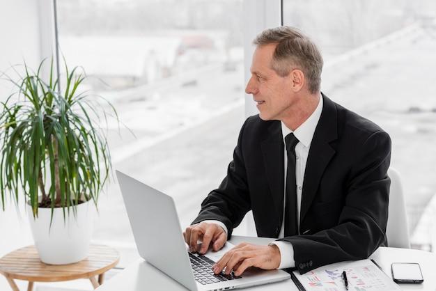 Hombre de negocios de alto ángulo que trabaja en la computadora portátil