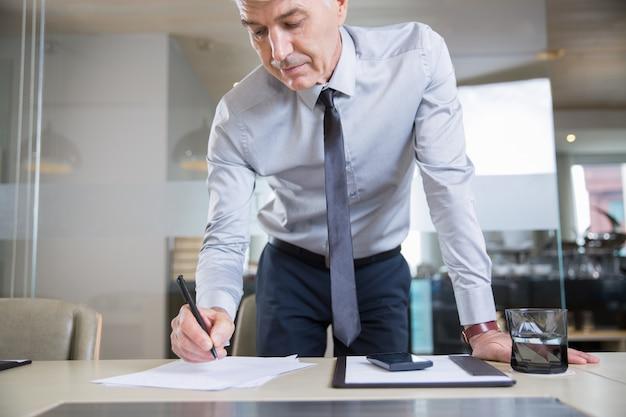 El hombre de negocios de alto nivel de flexión sobre el escritorio y escritura