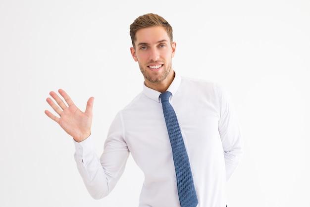 Hombre de negocios amigable saludando con la mano y mirando a la cámara