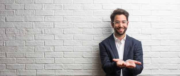 Hombre de negocios amistoso joven que lleva a cabo algo con las manos, mostrando un producto, sonriendo y alegre