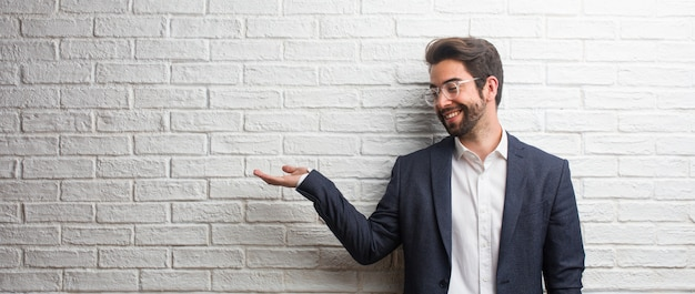 Hombre de negocios amistoso joven que lleva a cabo algo con las manos, mostrando un producto