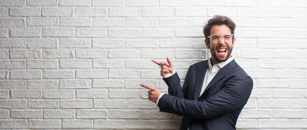 Hombre de negocios amistoso joven que señala al lado, sonriendo sorprendido presentando algo, natural e informal