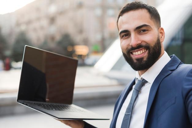 Hombre de negocios de ángulo bajo con laptop