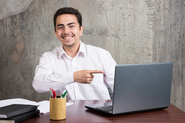 Hombre de negocios apuntando a la computadora portátil y sentado en el escritorio. foto de alta calidad