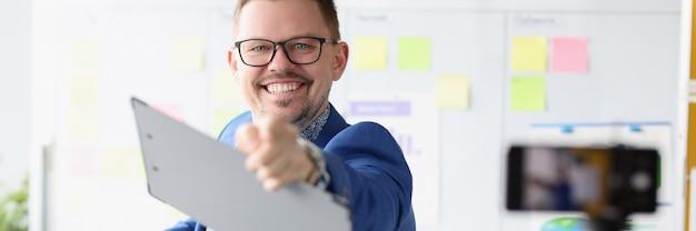Hombre de negocios apuntando con el dedo delante de la cámara del teléfono móvil cursos de negocios exitosos
