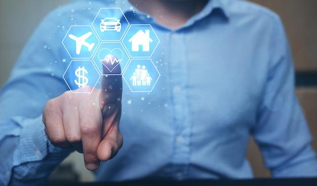 Hombre de negocios apuntando iconos digitales coche, viajes, familia, vida, casa y finanzas.