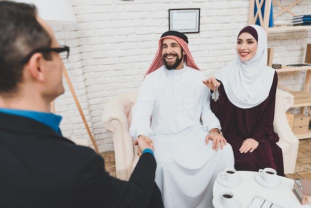 Hombre de negocios árabe apretón de manos esposa sostiene llaves de casa.