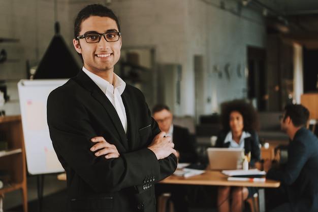 El hombre de negocios árabe con los brazos cruzados está sonriendo.