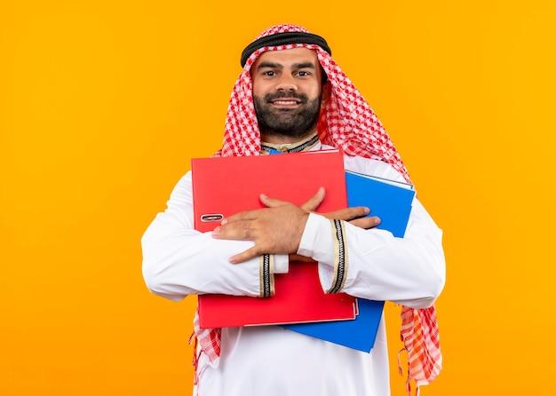 Hombre de negocios árabe complacido en ropa tradicional sosteniendo dos carpetas sonriendo confiado de pie sobre la pared naranja