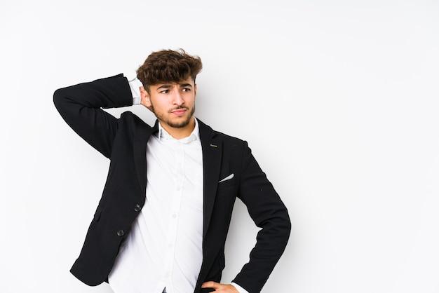 Hombre de negocios árabe joven aislado tocando la parte posterior de la cabeza, pensando y haciendo una elección.