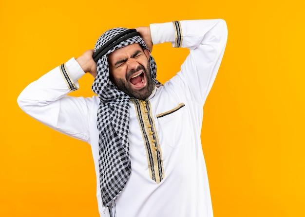 Hombre de negocios árabe en ropa tradicional gritando loco loco con expresión agresiva tocando sus manos de pie sobre la pared naranja