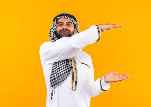 Hombre de negocios árabe en ropa tradicional mostrando letrero de gran tamaño, sonriendo, símbolo de medida de pie sobre la pared naranja