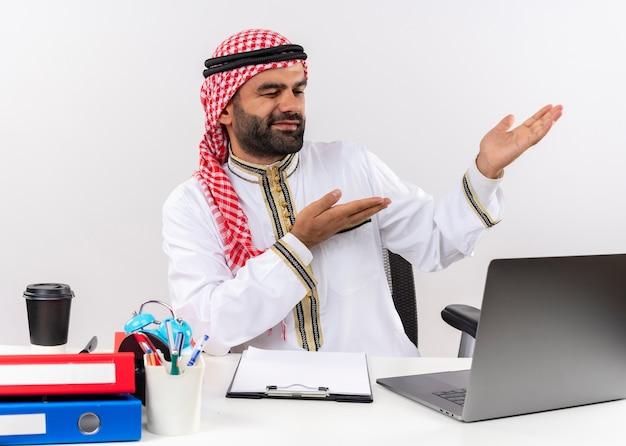 Hombre de negocios árabe en ropa tradicional sentado en la mesa con ordenador portátil apuntando con los brazos hacia el lado trabajando en la oficina