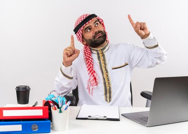 Hombre de negocios árabe en ropa tradicional sentado en la mesa con ordenador portátil apuntando con el dedo índice hacia arriba mirando confiado trabajando en la oficina