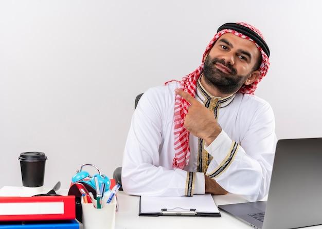 Hombre de negocios árabe en ropa tradicional sentado en la mesa con ordenador portátil apuntando con el dedo índice a la izquierda mirando confiado trabajando en la oficina