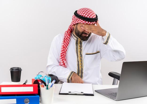 Hombre de negocios árabe en ropa tradicional sentado en la mesa con ordenador portátil con aspecto cansado y aburrido cubriendo los ojos con la mano trabajando en la oficina