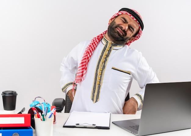 Hombre de negocios árabe en ropa tradicional sentado en la mesa con ordenador portátil con aspecto cansado tocando su espalda con dolor trabajando en la oficina