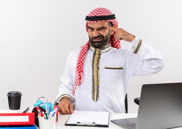 Hombre de negocios árabe en ropa tradicional sentado en la mesa con ordenador portátil guiñando un ojo apuntando su templo centrado en una tarea de trabajo en la oficina