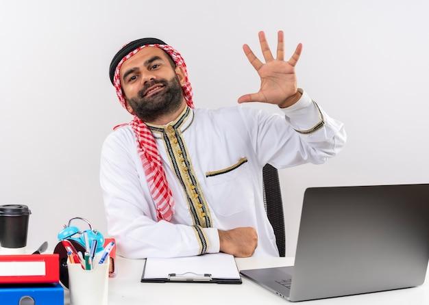Hombre de negocios árabe en ropa tradicional sentado en la mesa con ordenador portátil mostrando y apuntando hacia arriba con los dedos número cinco sonriendo trabajando en la oficina