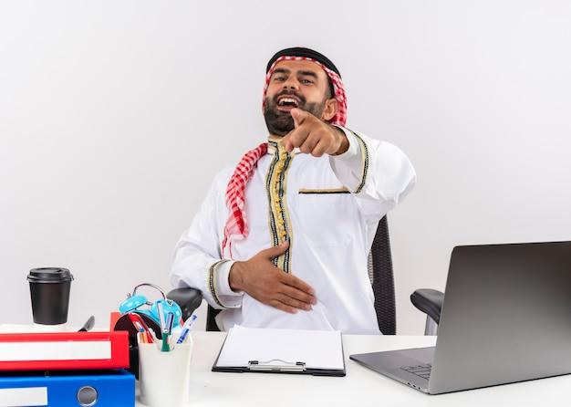 Hombre de negocios árabe en ropa tradicional sentado en la mesa con ordenador portátil riendo apuntando con el dedo a usted trabajando en la oficina