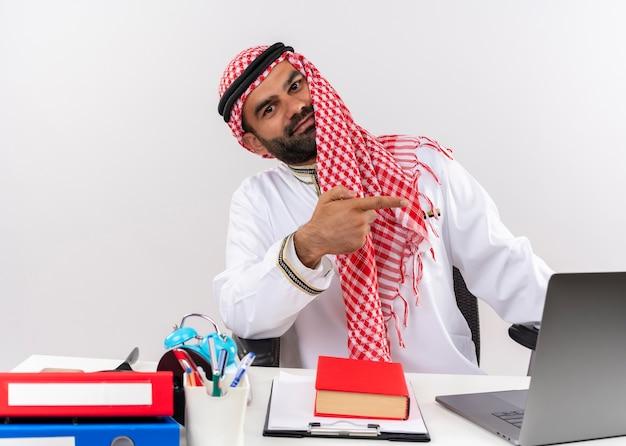 Hombre de negocios árabe en ropa tradicional sentado en la mesa con ordenador portátil sonriendo confiado apuntando con el dedo hacia el lado trabajando en la oficina