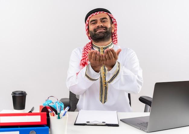 Hombre de negocios árabe en ropa tradicional sentado en la mesa con ordenador portátil tomados de la mano juntos pidiendo dinero trabajando en la oficina