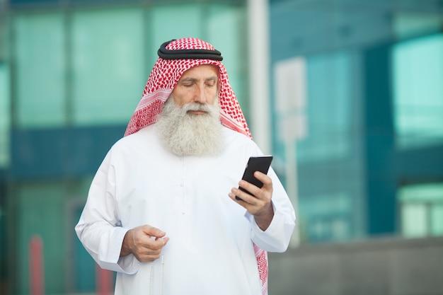 Hombre de negocios árabe trabajando con su teléfono en una calle en el fondo