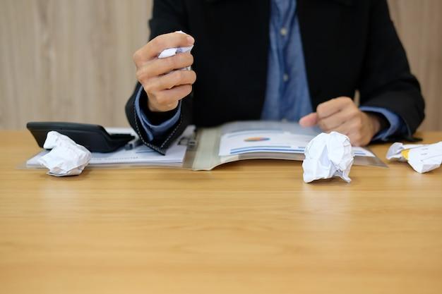 El hombre de negocios arruga el papel y se siente furioso, frustrado y estresado por el trabajo duro