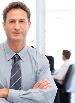 Hombre de negocios asertivo de pie delante de su equipo mientras trabajaba en una mesa