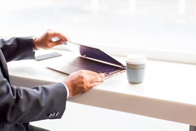 Hombre de negocios de asia que trabaja con la computadora portátil mientras está sentado cafetería. concepto de jóvenes empresarios