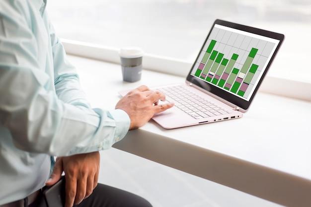 Hombre de negocios de asia que trabaja con el ordenador portátil mientras que sienta la cafetería