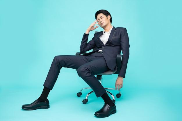 Hombre de negocios asiático agotado y frustrado sentado en la silla de oficina aislado sobre fondo verde