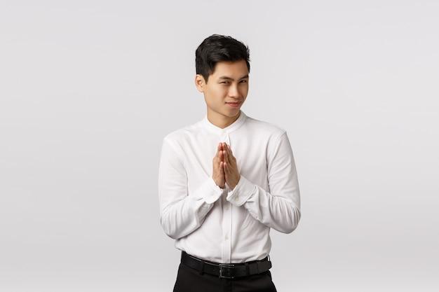 Hombre de negocios asiático apuesto joven misterioso y desviado en camisa blanca, pantalones, frotarse las manos y entrecerrar los ojos, tener un plan secreto malvado, saborear un buen trato, ganar dinero, estar de pie