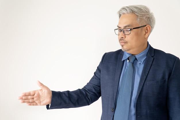 Hombre de negocios asiático confiado del retrato que lleva los vidrios y el apretón de manos azul del traje en blanco