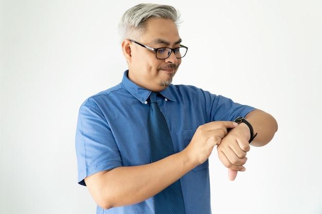 Hombre de negocios asiático confiado del retrato que lleva los vidrios y la camisa de manga corta que mira el reloj en blanco