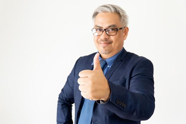 Hombre de negocios asiático confiado del retrato que lleva los vidrios y el traje azul que presentan con la mano en blanco