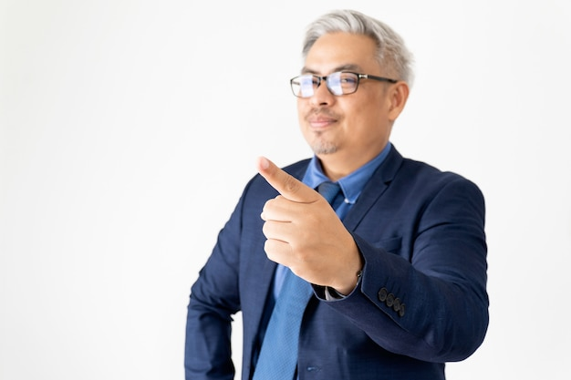 Hombre de negocios asiático confiado del retrato que lleva los vidrios y el traje azul que señalan con la mano en blanco