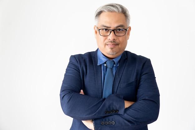 El hombre de negocios asiático confiado del retrato que llevaba los vidrios y los brazos azules del traje cruzaron en blanco
