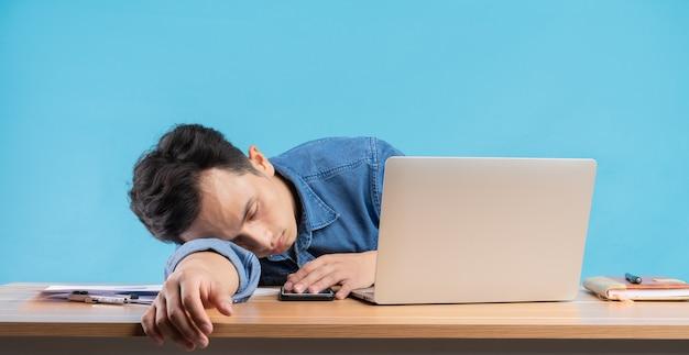 Hombre de negocios asiático dejó caer la cabeza sobre la mesa debido a la presión en el trabajo