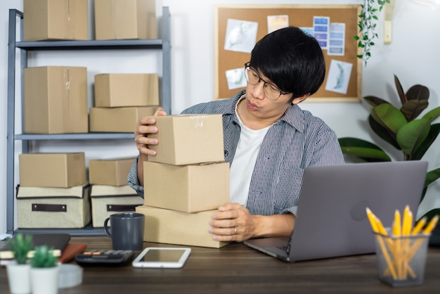 Hombre de negocios asiático, emprendedor o emprendedor independiente que trabaja en una caja de cartón, prepara la caja de entrega para el concepto de cliente, venta en línea, comercio electrónico, embalaje y envío.
