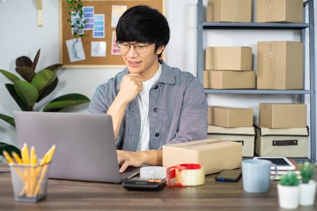 Hombre de negocios asiático emprendedor pyme o autónomo que trabaja en una caja de cartón prepara la caja de entrega para el cliente, la venta en línea, el comercio electrónico, el concepto de embalaje y envío.