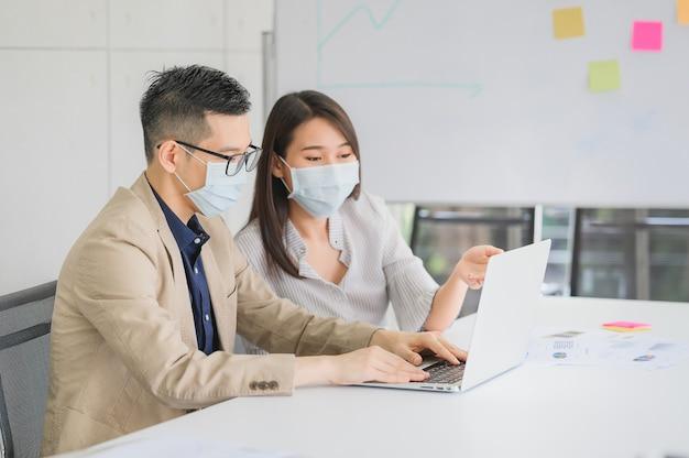 Hombre de negocios asiático y empresaria usa mascarilla para proteger el coronavirus discutir proyecto comercial