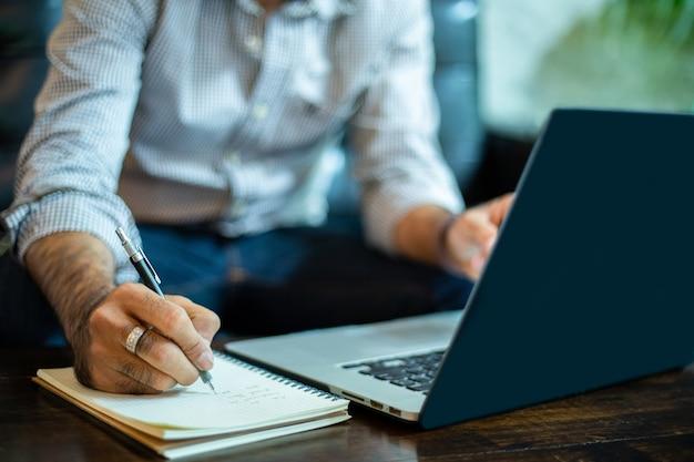 Hombre de negocios asiático escribir notas y usar la computadora portátil para trabajar en la oficina en casa.