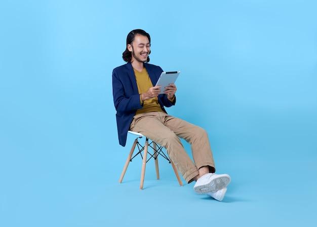 Hombre de negocios asiático feliz sonriendo usando una tableta digital mientras está sentado en una silla en azul brillante.