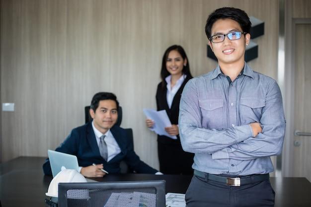 Hombre de negocios asiático y grupo usando el cuaderno para reuniones y hombres de negocios sonriendo felices por trabajar