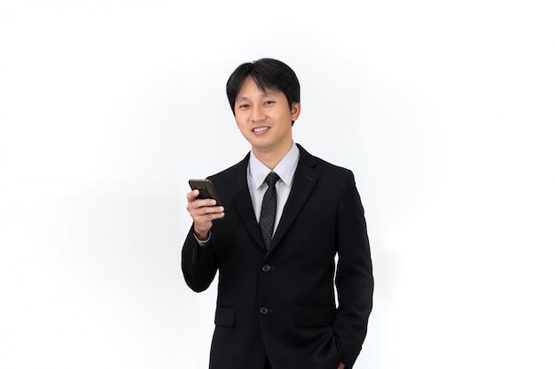 Hombre de negocios asiático hermoso que usa el teléfono móvil en el fondo blanco