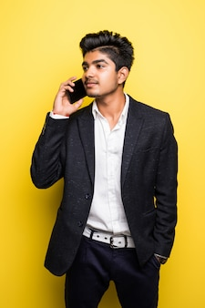 Hombre de negocios asiático hombre guapo wi hablar por teléfono inteligente en la pared amarilla
