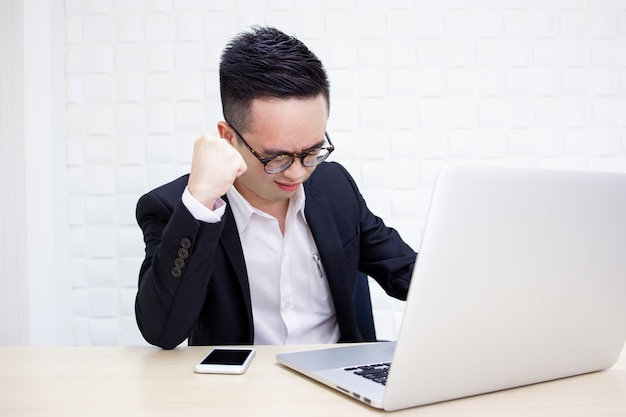 Hombre de negocios asiático infeliz que sufre de trabajar duro durante mucho tiempo.